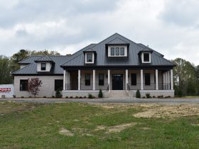 House facade featuring white brick porch and black metal roof.