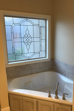 Master bath with corner jacuzzi tub and Scottish stained glass window.