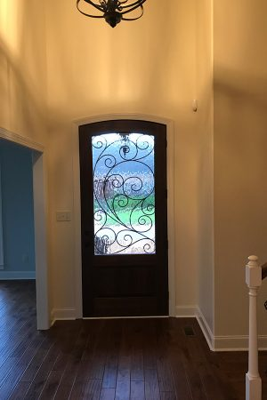 Home foyer and front door with stained glass panel.