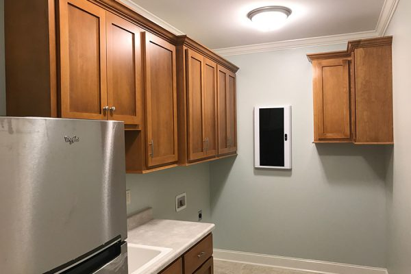 Laundry washroom with sink, washer/dryer hookups, cabinets, and fridge.