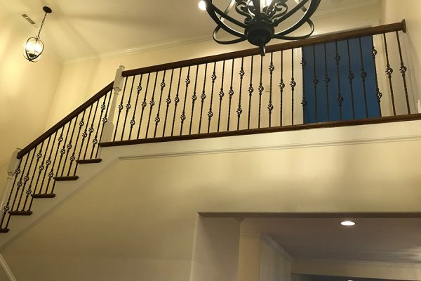 Lofted stair landing with decorative iron spindles.