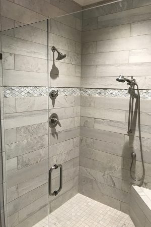 Master bathroom tiled shower stall with bench and clear glass door.