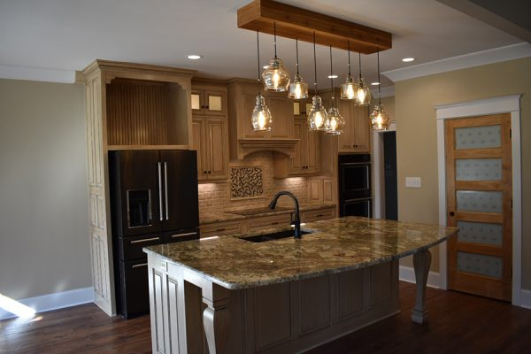 Luxury kitchen that includes a glass flat top stove, double oven, double door fridge, and pantry.