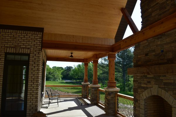 Outdoor living area and back porch featuring a stone fireplace.