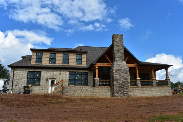 Rear exterior of house featuring an outdoor living space and stone fireplace.