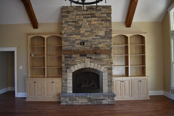 Living room with a stone fireplace and custom built-ins.