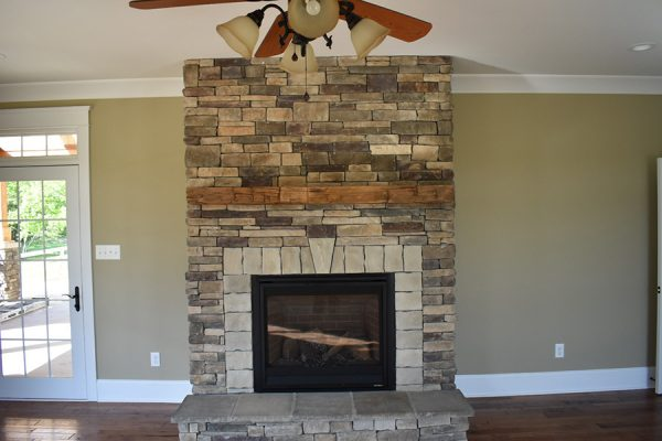 Stone fireplace with a wooden mantel.