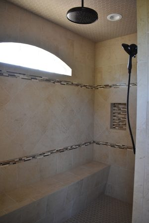 Luxury tiled shower with bench and rain shower head.