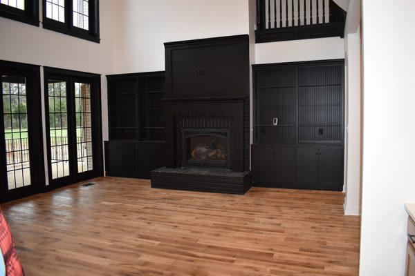 Living room with black fireplace and custom black built-ins.