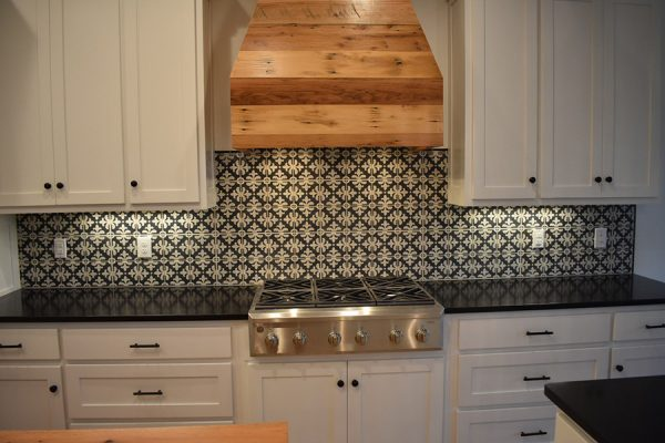 Kitchen tiled backsplash with wooden range hood.