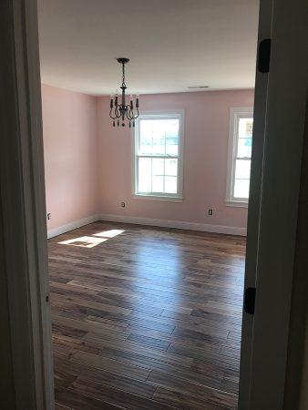 Pink children's bedroom with small chandelier.