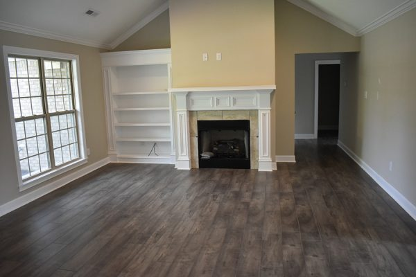 Living room with large white mantel fireplace and white built-in shelves.