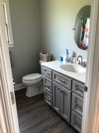 Full Bathoom with grey cabinets and marble countertop.