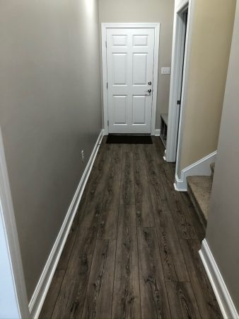 Hallway to back door with wood floor and carpeted stairs.