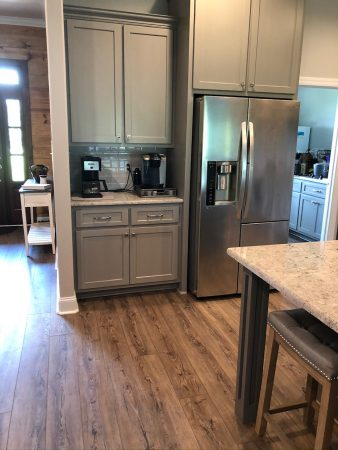 Kitchen wet bar or coffee bar next to stainless steel fridge.