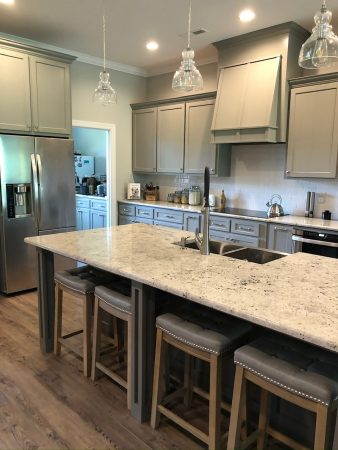 Kitchen island with marbled granite counter top and glass Edison bulb pendants.