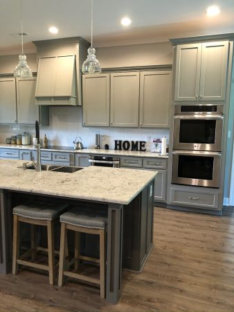 Kitchen with grey cabinets, island, and double ovens.
