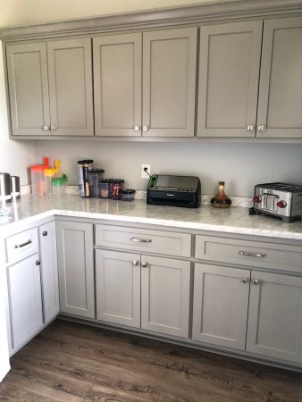 Kitchen corner with grey cabinets and marbled granite countertop.