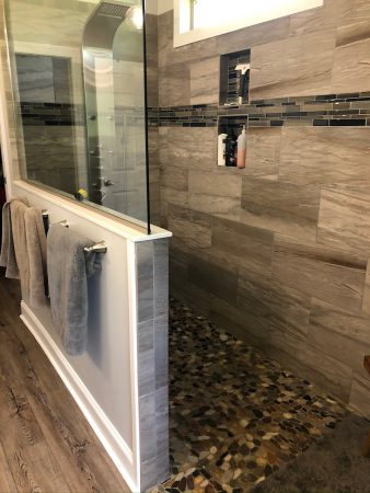 Master bathroom with walk in shower that has wood tiled wall and a pebble tile floor