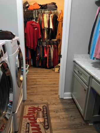 Washroom or laundry room with faux marble counter top leading to closet.